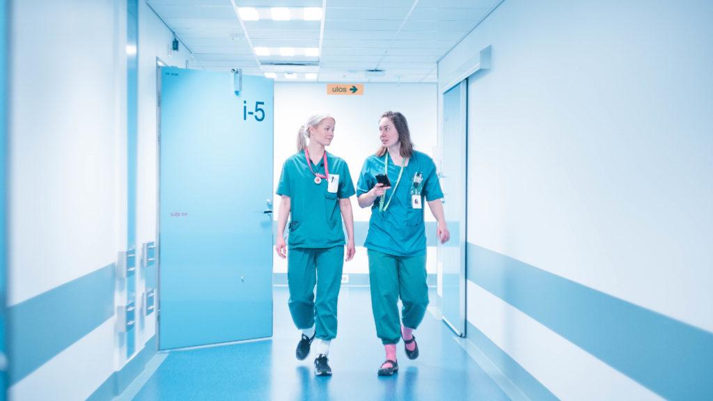 Kaksi sairaanhoitajaa kävelevät käytävällä
