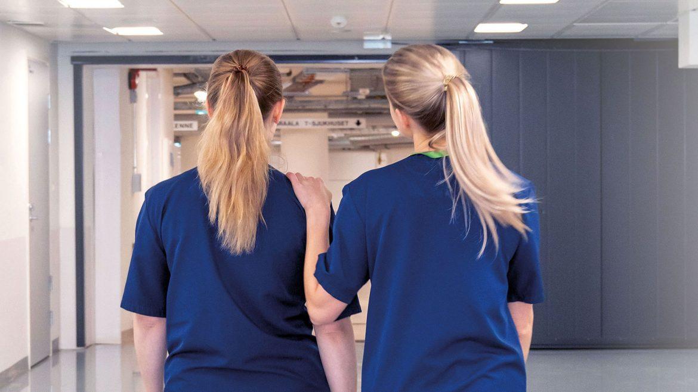 Zwei Krankenschwestern im Krankenhausflur haben weniger Zeitdruck durch Pflege-App
