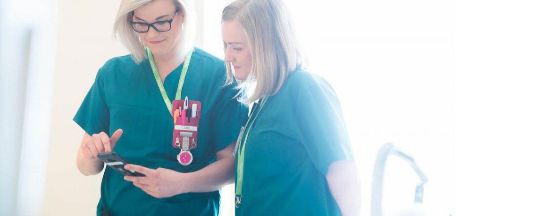 Zwei Krankenschwestern nutzen die  App für Pflegekräfte im Behandlungszimmer